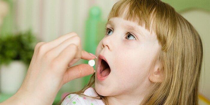 На фото: прием таблетки ребенком